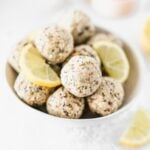 lemon poppy seed balls in a white bowl with lemon slices.