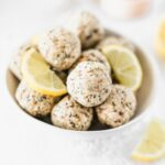 lemon poppy seed balls in a white bowl with lemon slices.