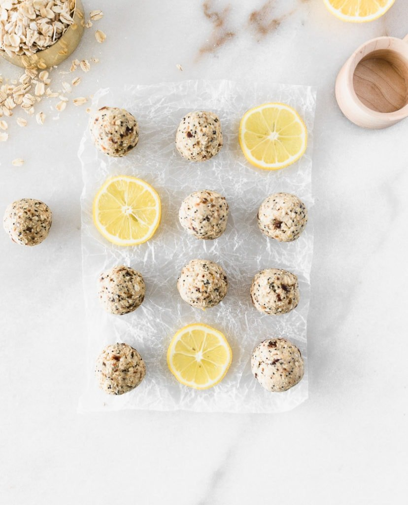 overhead view of lemon poppy seed snack balls on a white background with lemon slices.