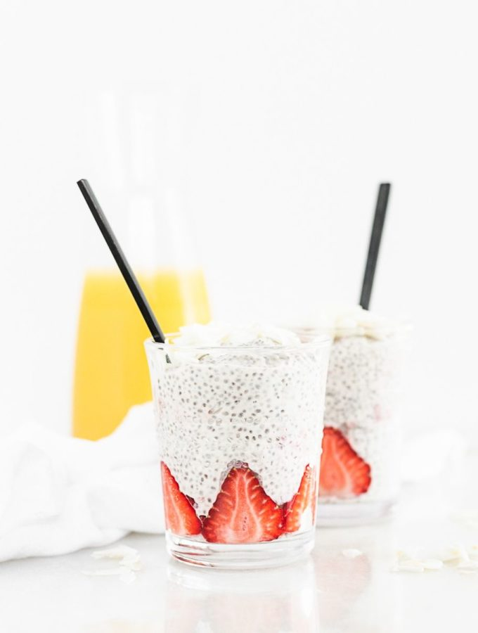 two glasses with coconut orange strawberry chia pudding with black spoons in them and a carafe of orange juice behind them.