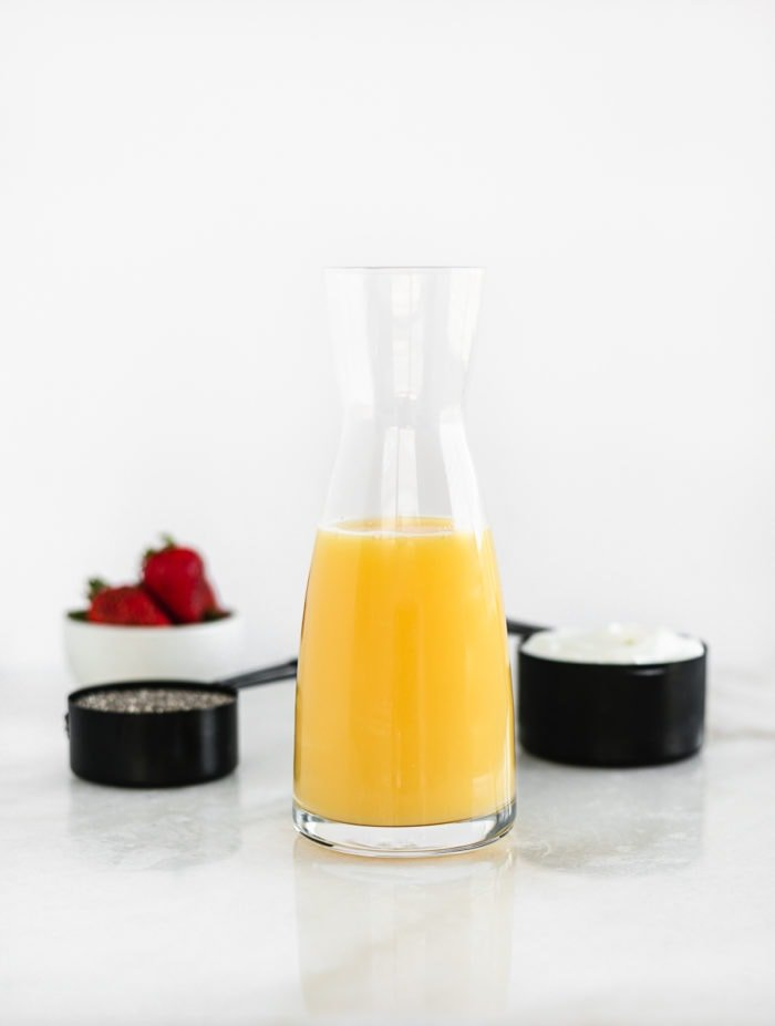 orange juice carafe with cups of yogurt, chia seeds and strawberries behind it.