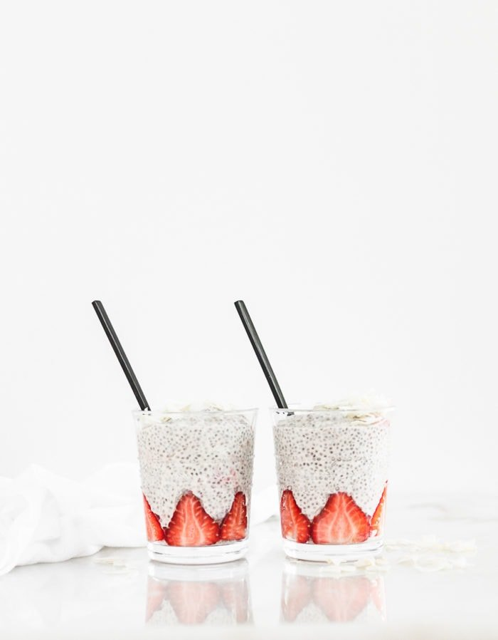 two glasses of strawberry orange chia pudding with black spoons in them.