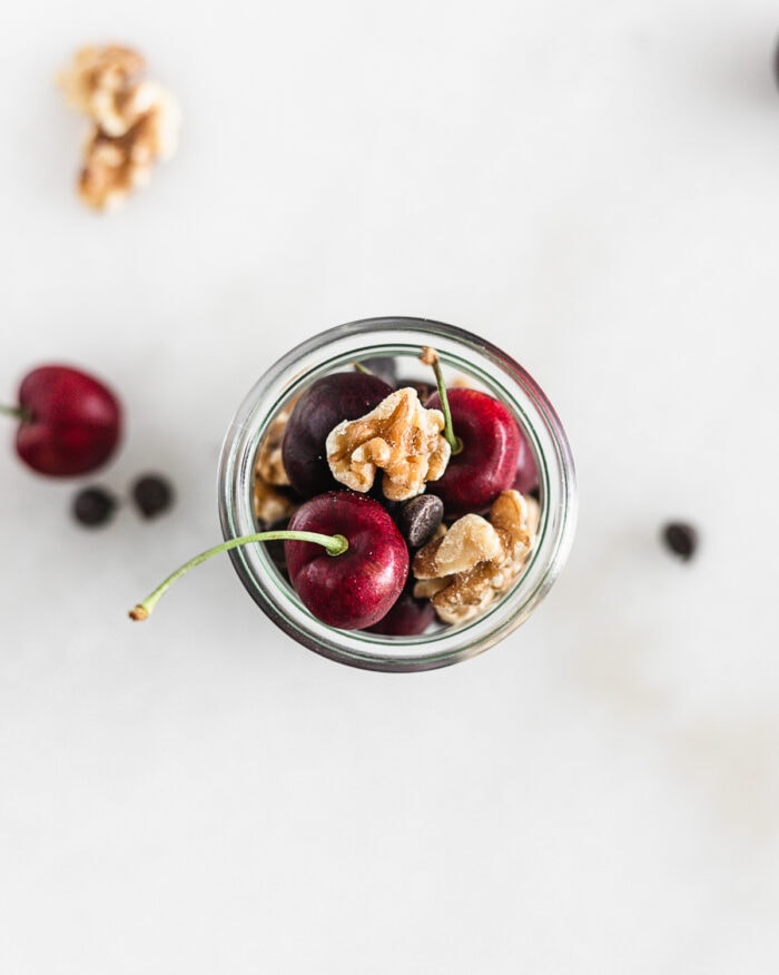 overhead view of cherries, walnuts and chocolate chips in a glass jar.