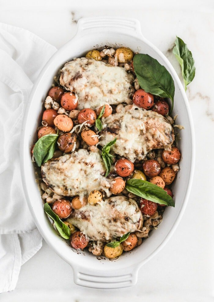 overhead view of white oval baking dish with mozzarella covered chicken, tomatoes, and basil on top of farro.