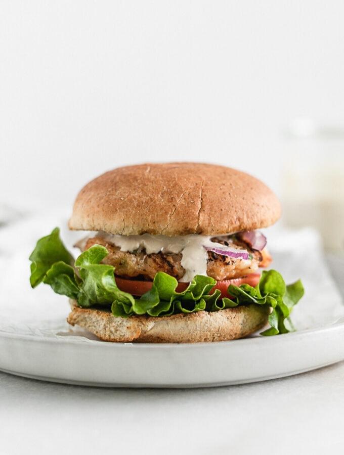 shrimp caeser burger on a wheat bun on a grey plate.