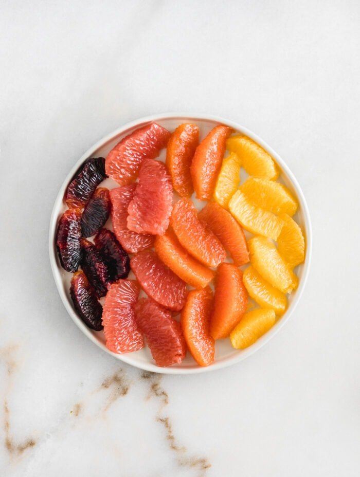 blood orange, grapefruit, cara cara and navel orange segments on a whhite plate against a white marble background.