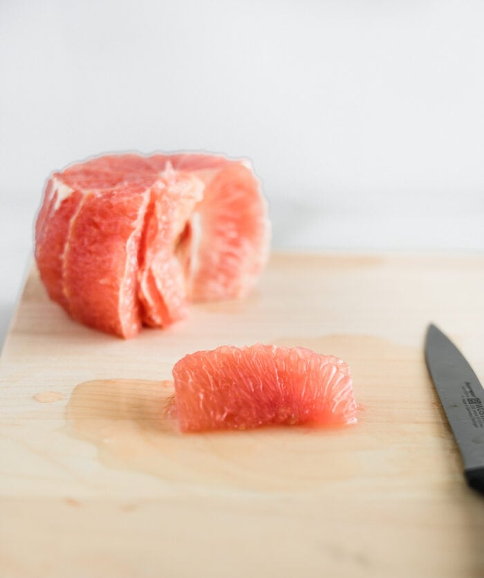 grapefruit segment on a wooden cutting board with a grapefruit behind it.