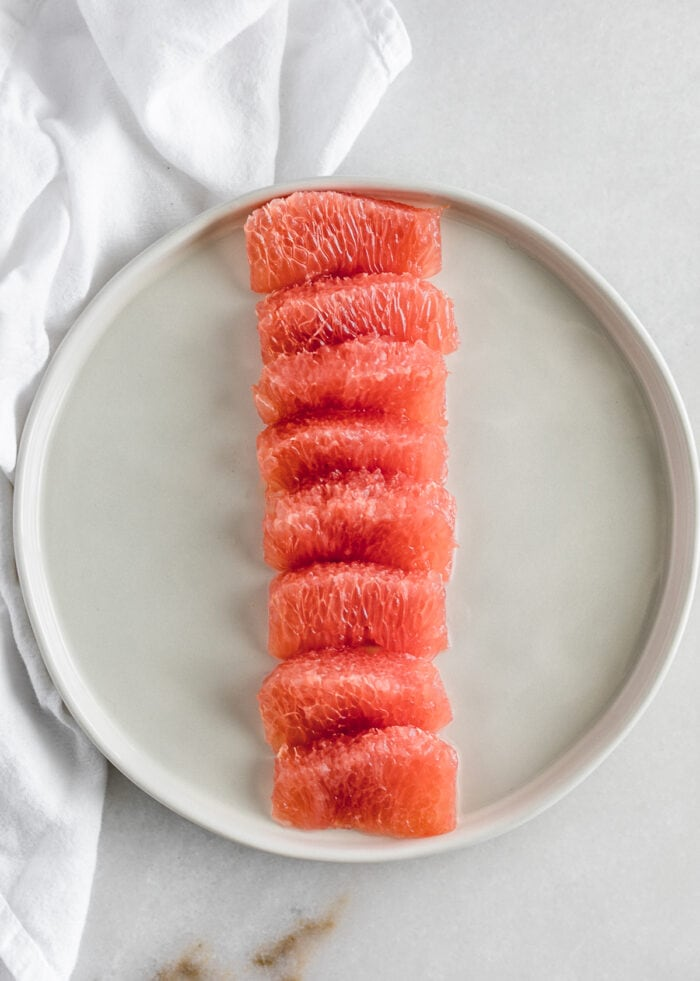 grapefruit segments in a straight line on a white plate.