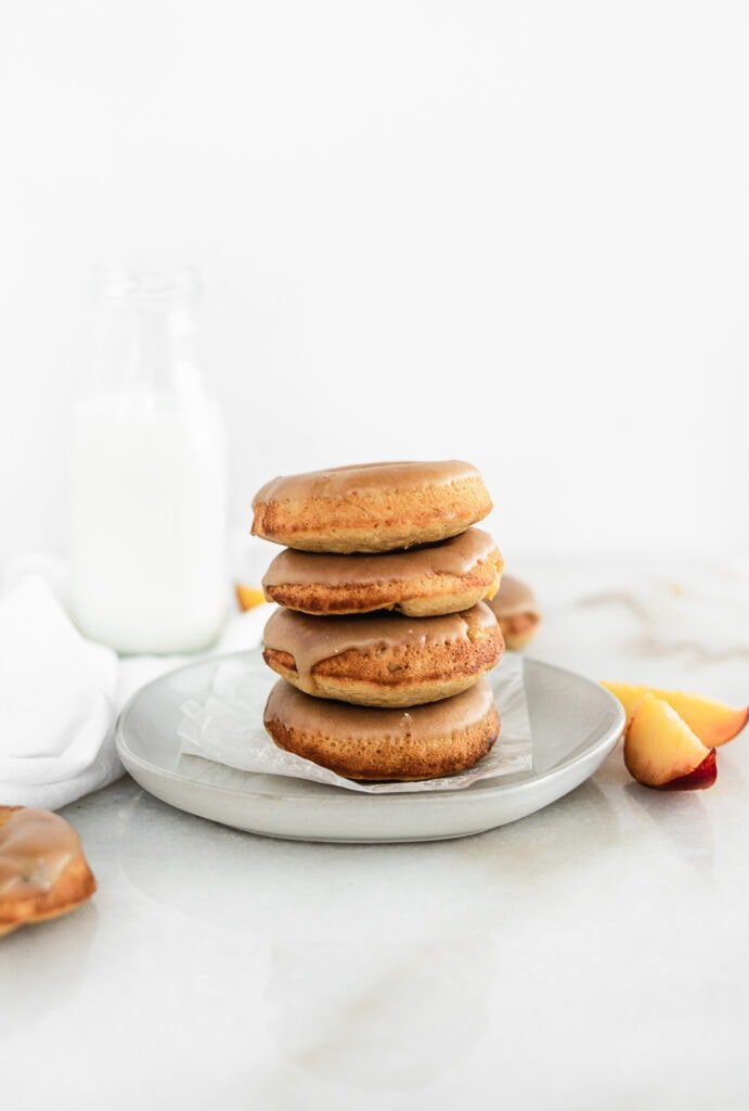 four baked peach donuts with brown sugar glaze stacked on a plate with a bottle of milk in the background and peaches.