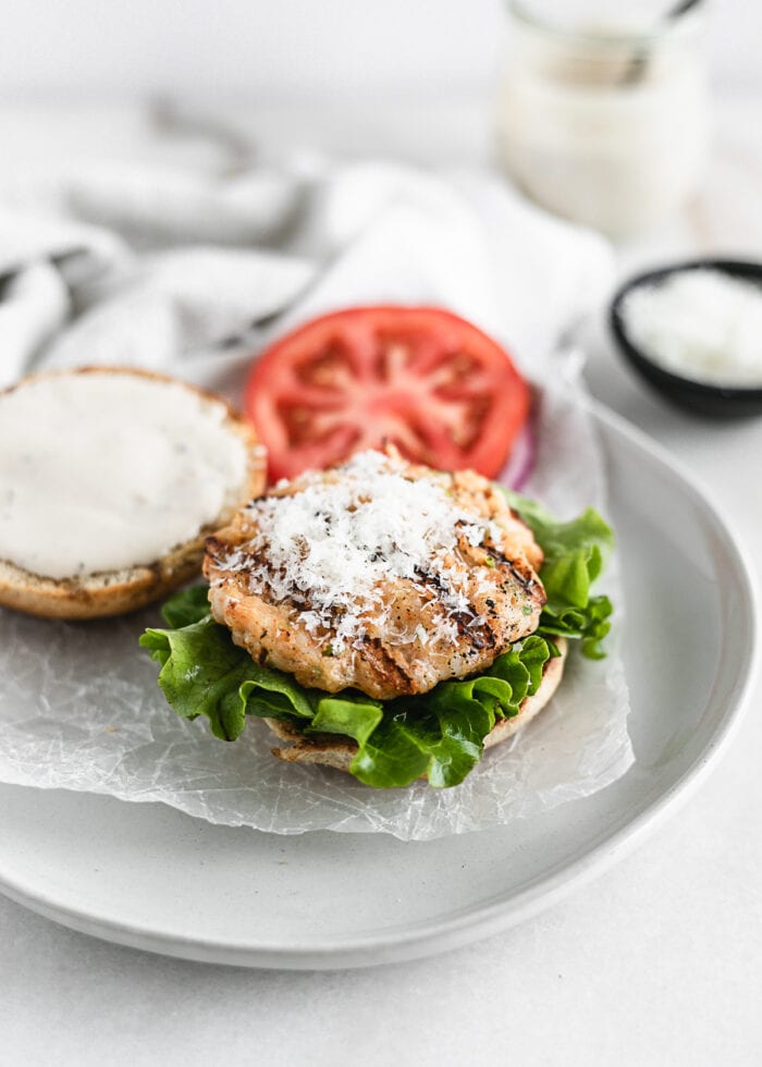 Grilled shrimp Caesar burger patty on a bun with lettuce, topped with shaved parmesan, with a tomato slice and the top bun topped with Cesar dressing behind it.