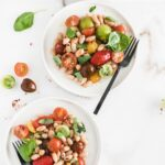 overhead image of two white plates with tomato white bean salad on them with a black fork on one plate and tomatoes and basil around the plates.
