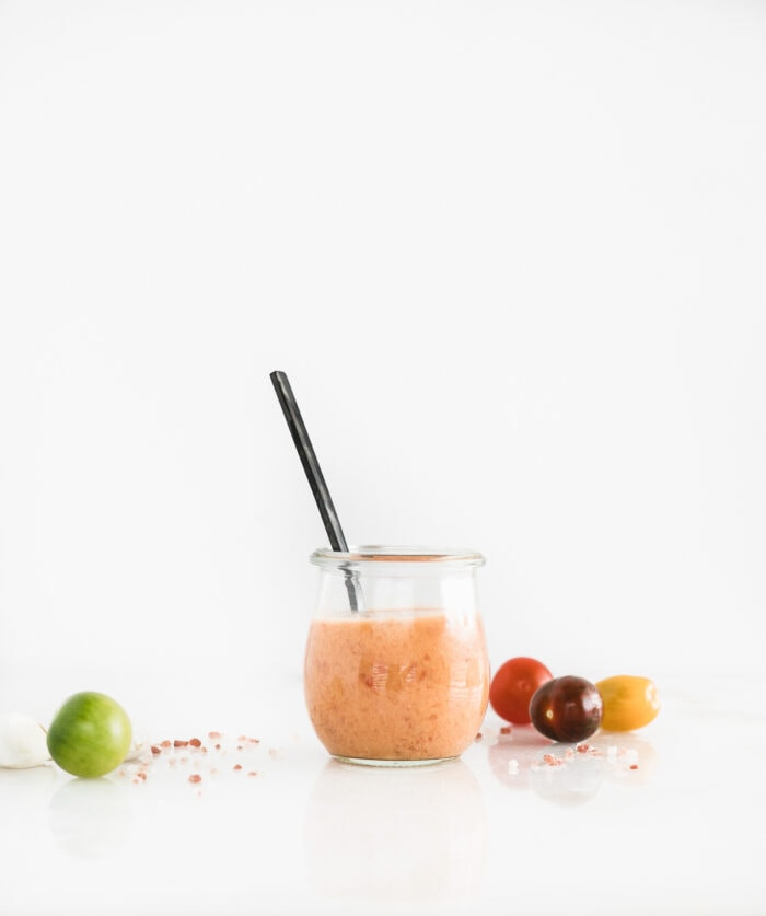 glass jar with tomato vinaigrette and a black spoon in it, surrounded by colorful mini tomatoes.