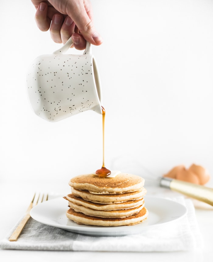 stack of buttermilk pancakes on a white plate with a hand pouring maple syrup on top.