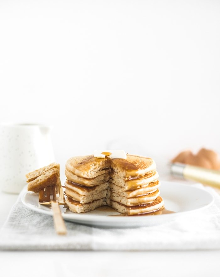 stack of whole wheat buttermilk pancakes with a bite cut out on a gold fork.