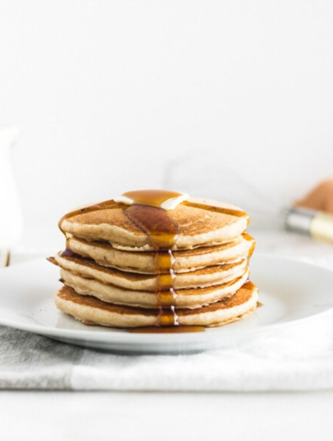 stack of buttermilk pancakes on a white plate with syrup dripping down the front.