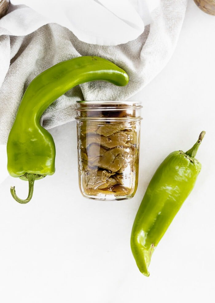 jar of roasted hatch chiles on a white background with two fresh chiles on either side of it.