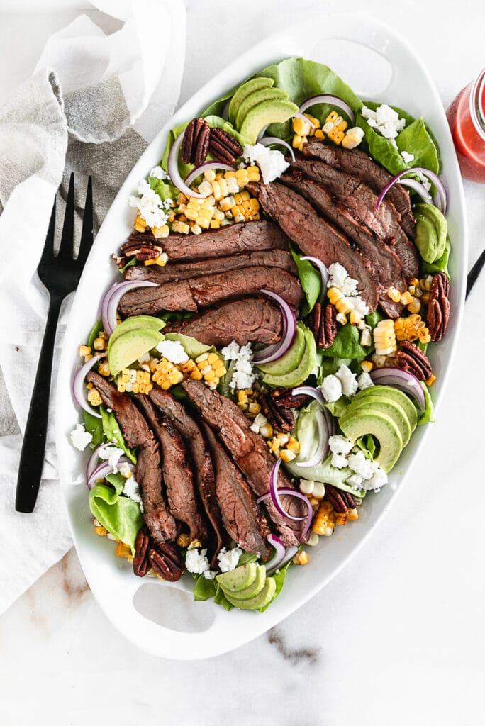 overhead view of raspberry chipotle flank steak salad on a white oval platter with a black serving fork.