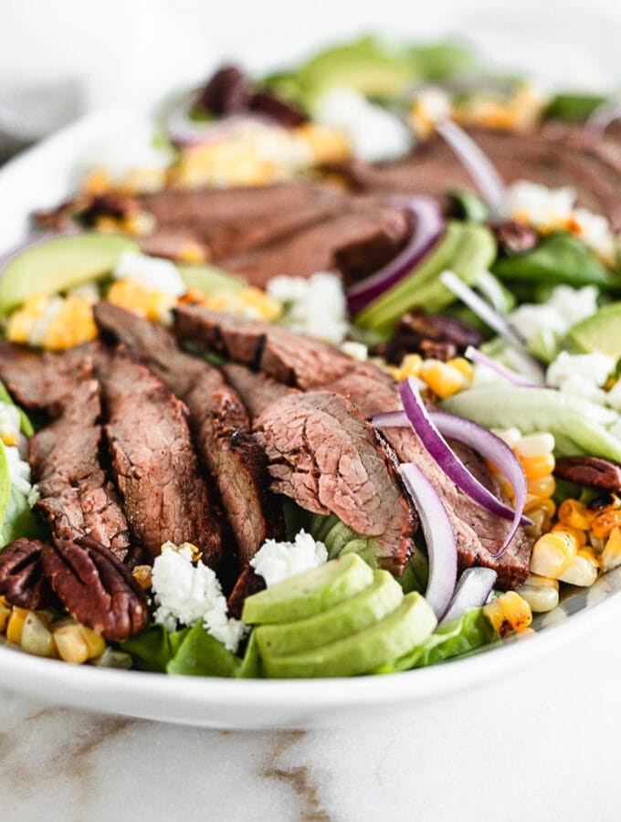 sliced grilled flank steak, avocado, grilled corn and red onion on a salad on a white platter.