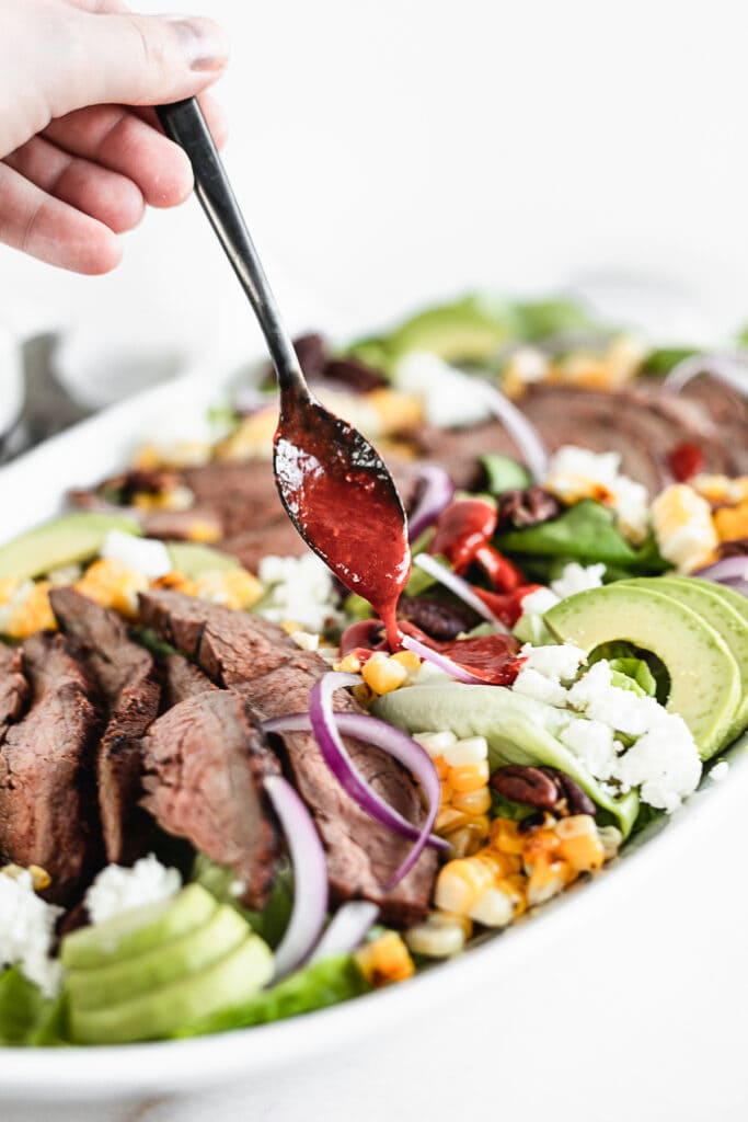 raspberry chipotle dressing being spooned over a flank steak salad with a small black spoon.