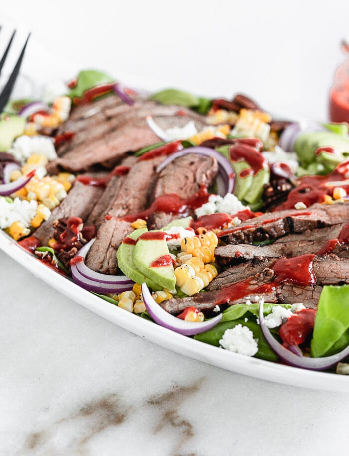 closeup of sliced grilled flank steak on a salad with sliced avocado grilled corn, goat cheese and pecans drizzled with raspberry chipotle dressing.