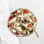 overhead view of greek orzo pasta salad in a white bowl with a gold spoon.