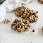 three zucchini oatmeal breakfast cookies on a piece of parchment paper with a white napkin and zucchini in the background.