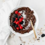 overhead view of a bowl of chocolate oatmeal topped with berries with a gold spoon in it.