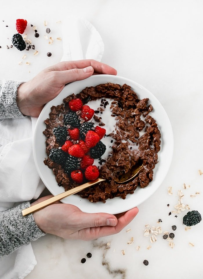 overhead view of hands holding a bowl of chocolate oatmeal topped with berries.