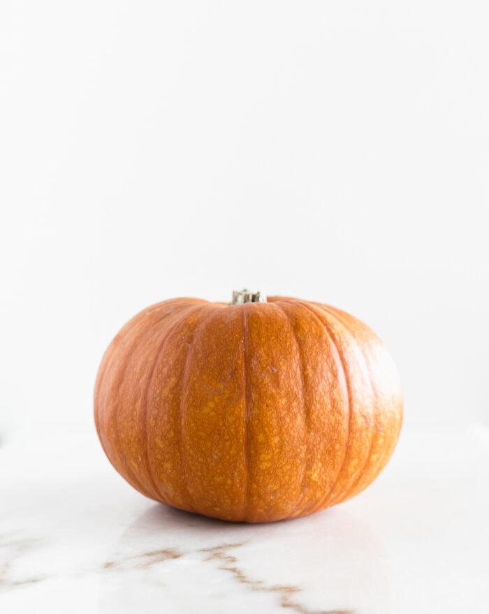 whole sugar pumpkin on a white background.