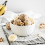 banana bread snack balls in a white bowl on top of a metal rack with banana slices and walnuts around it.