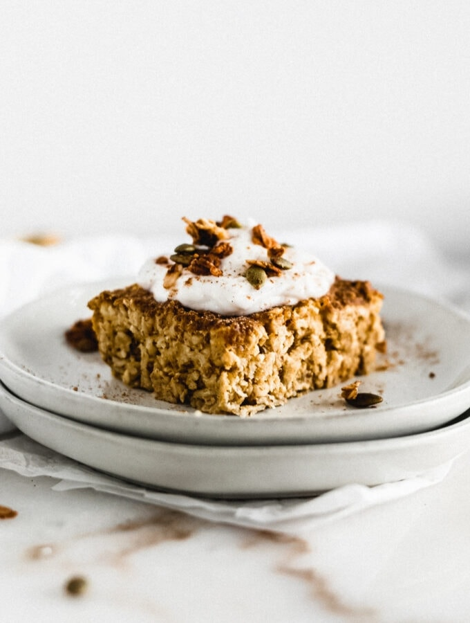 square of pumpkin baked oatmeal topped with yogurt and granola on a stack of grey plates.