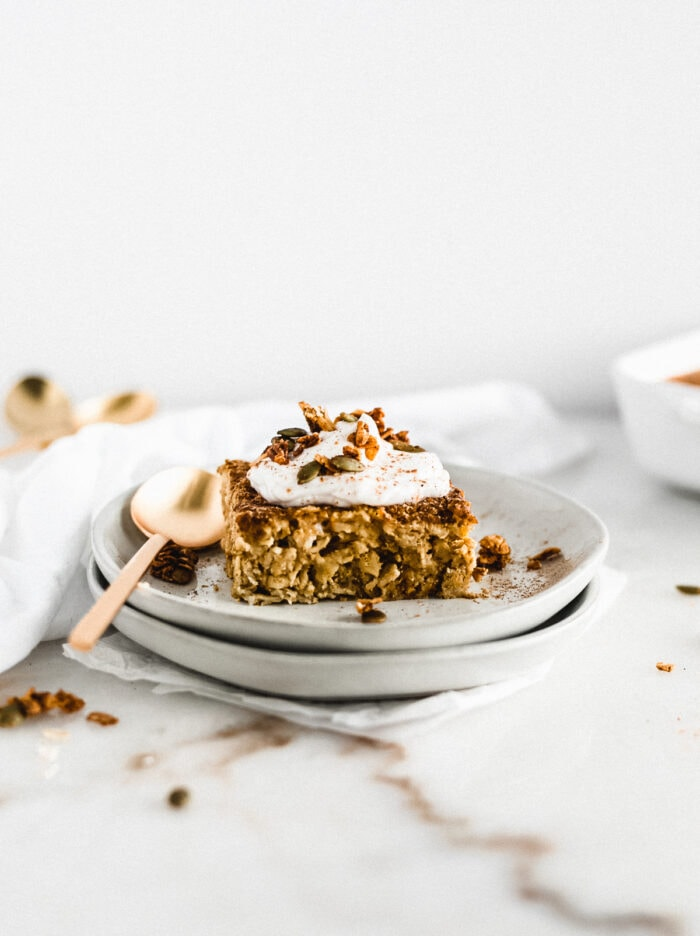square of pumpkin baked oatmeal topped with yogurt and granola on a stack of grey plates with a gold spoon..
