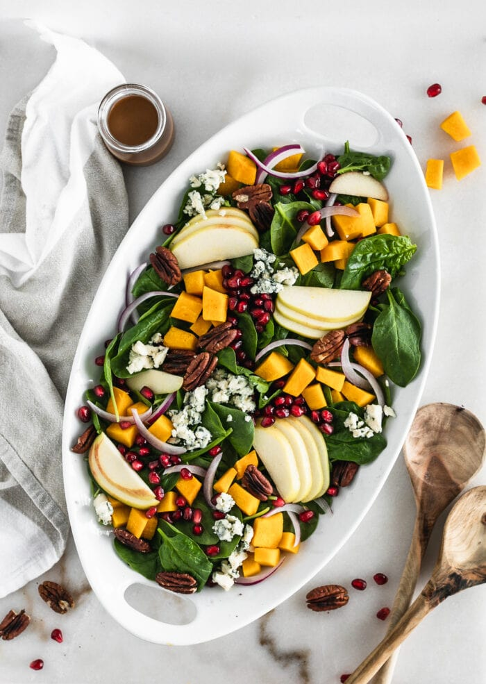 overhead view of pumpkin spinach salad on a white oval serving dish.