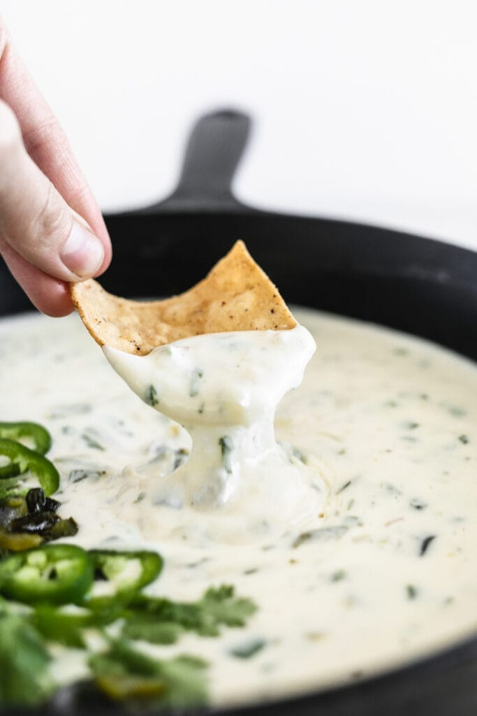closeup of a hand dipping a chip into poblano queso blanco.