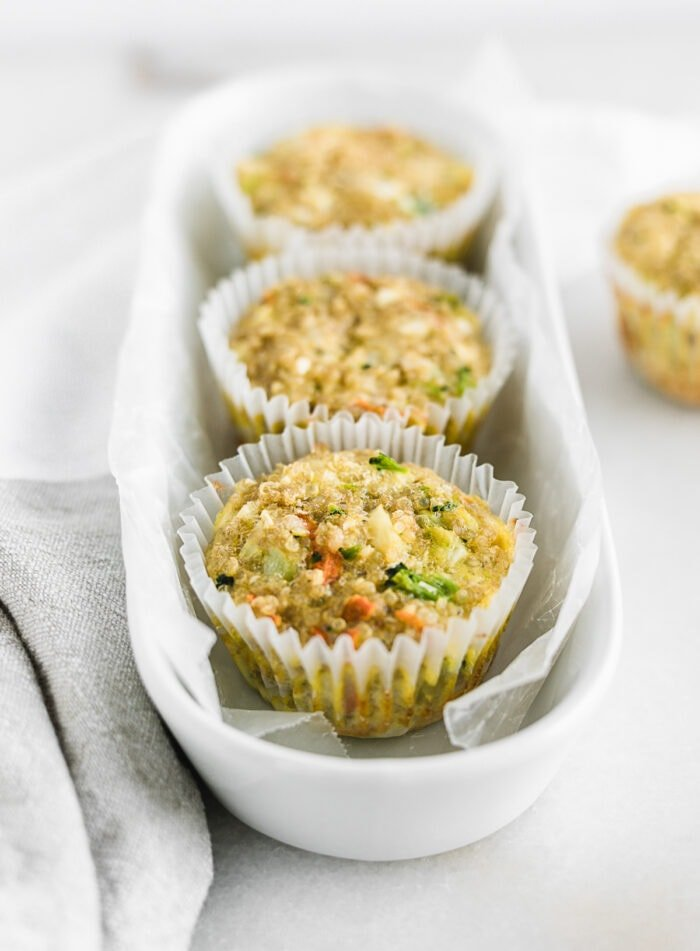 veggie quinoa egg muffins lined up in a white oval dish.