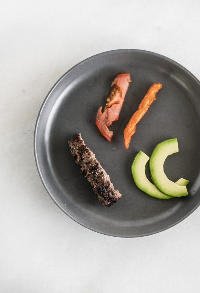 grey plate with strips of hamburger, tomato, sweet potato and avocado.