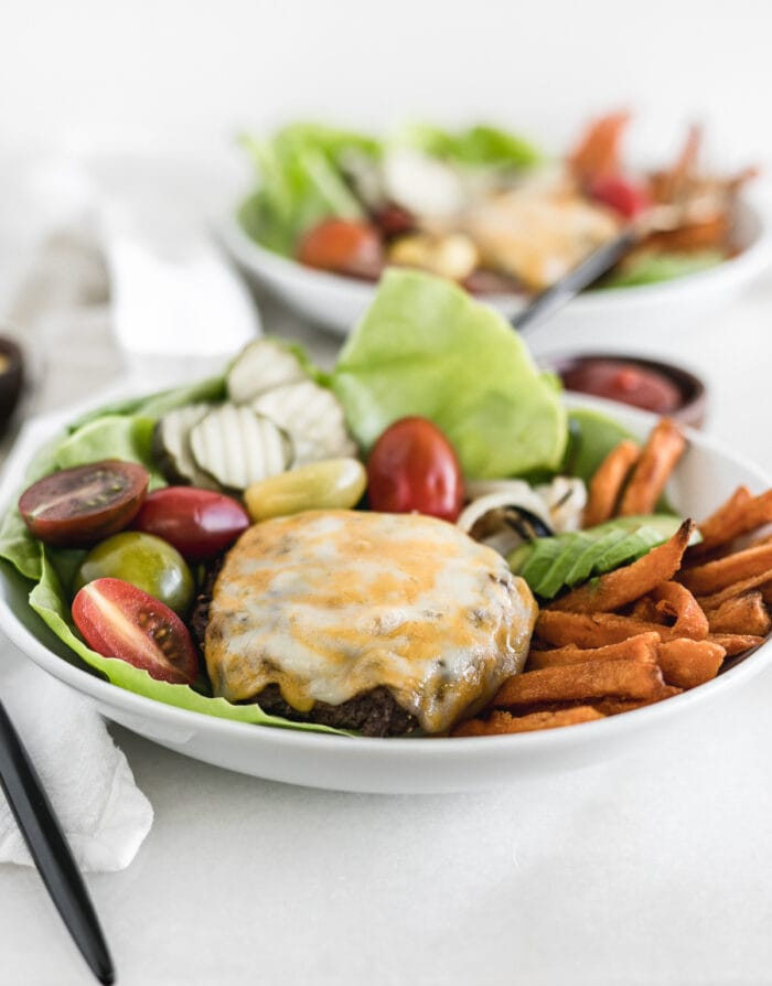 grilled hamburger patty with cheese on top of vegetables and sweet potato fries in a white bowl.