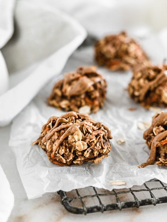 carrot apple breakfast cookies on a piece of parchment on a cooling rack.