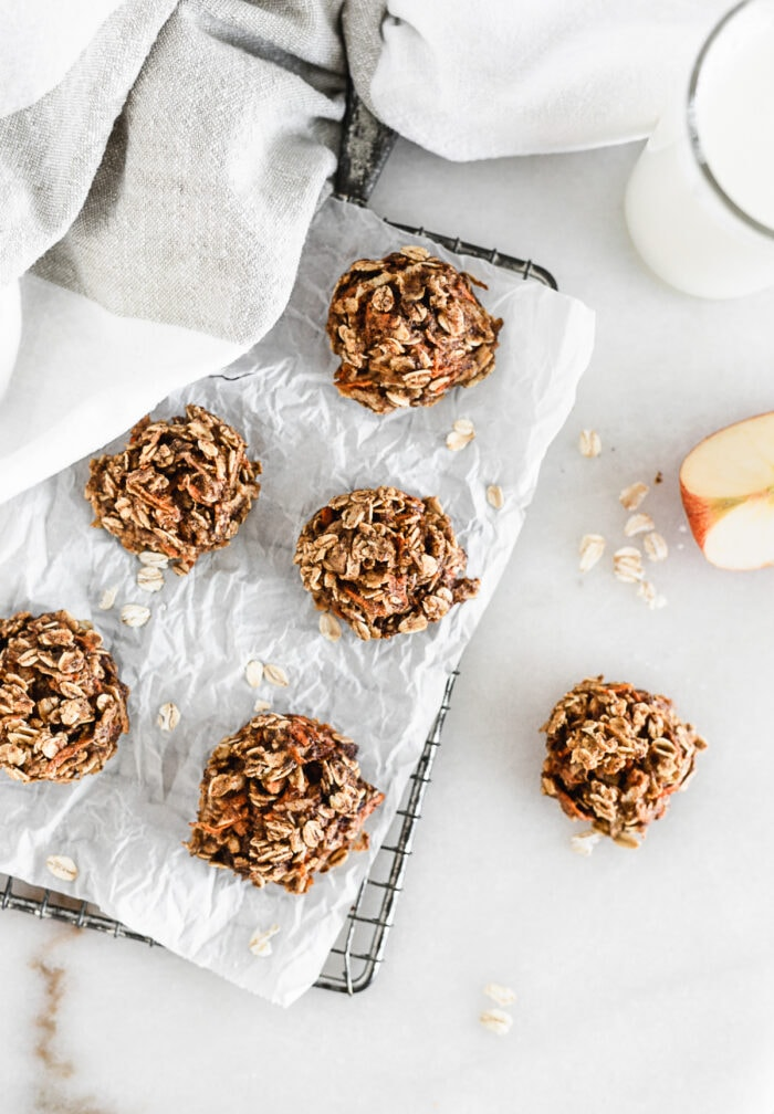 overhead view of carrot apple breakfast cookies on a piece of parchment on top of a cooling rack.