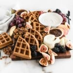 fall brunch board with waffles, yogurt, fruit and cheese on a white marble background.