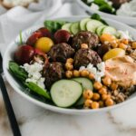 meatballs, cucumbers, hummus, feta and vegetables in a white bowl.
