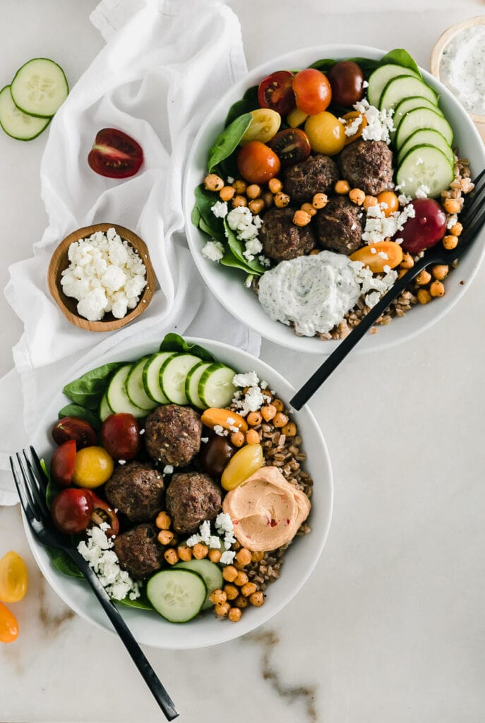 Overhead view of two mediterranean meatball bowls with black forks on a white background.