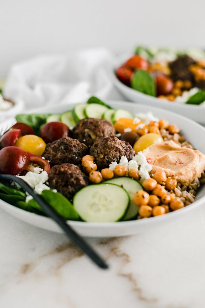 closeup of a grain bowl with mediterranean meatballs, cucumber, hummus and chickpeas in a white bowl with a black fork.