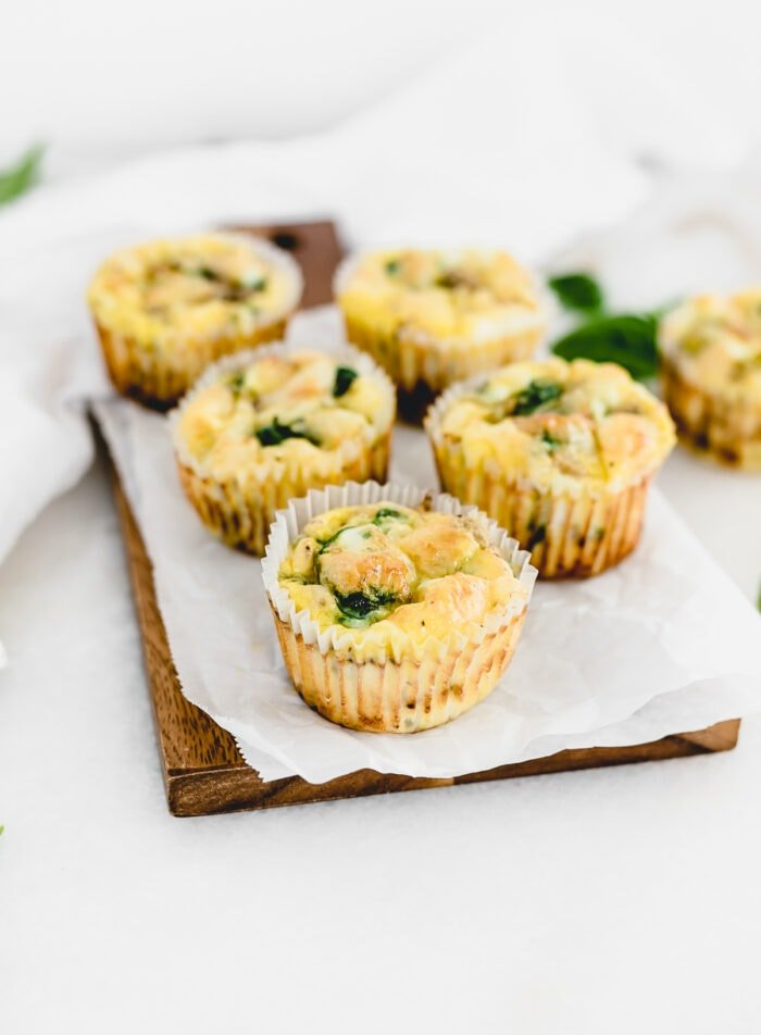 mushroom spinach egg muffins on a wooden serving board.
