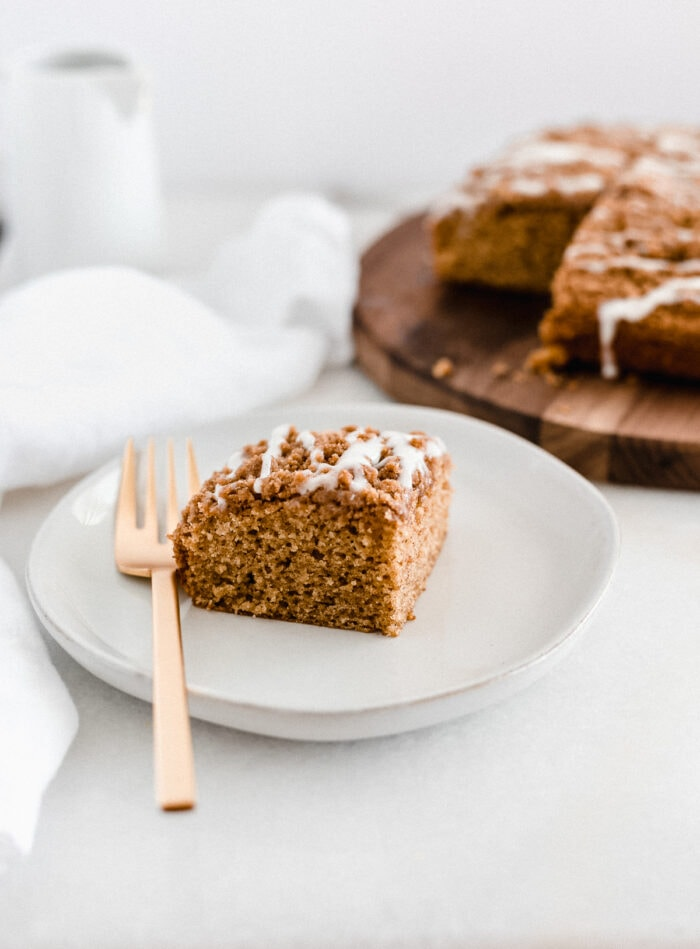 square of pumpkin coffee cake on a white plate with a gold fork and the rest of the cake in the background.