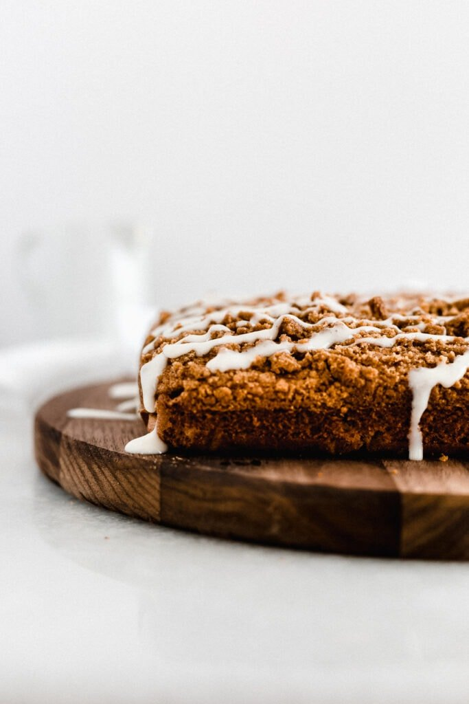 pumpkin coffee cake with streusel topping and cream cheese icing on a round wooden cutting board.