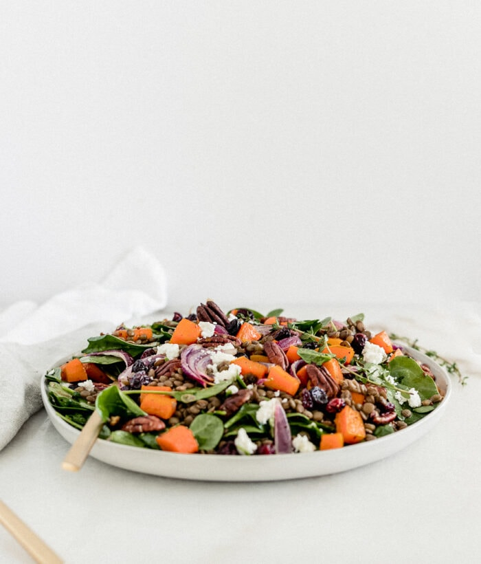 butternut squash lentil spinach salad on a large grey plate with a gold fork.