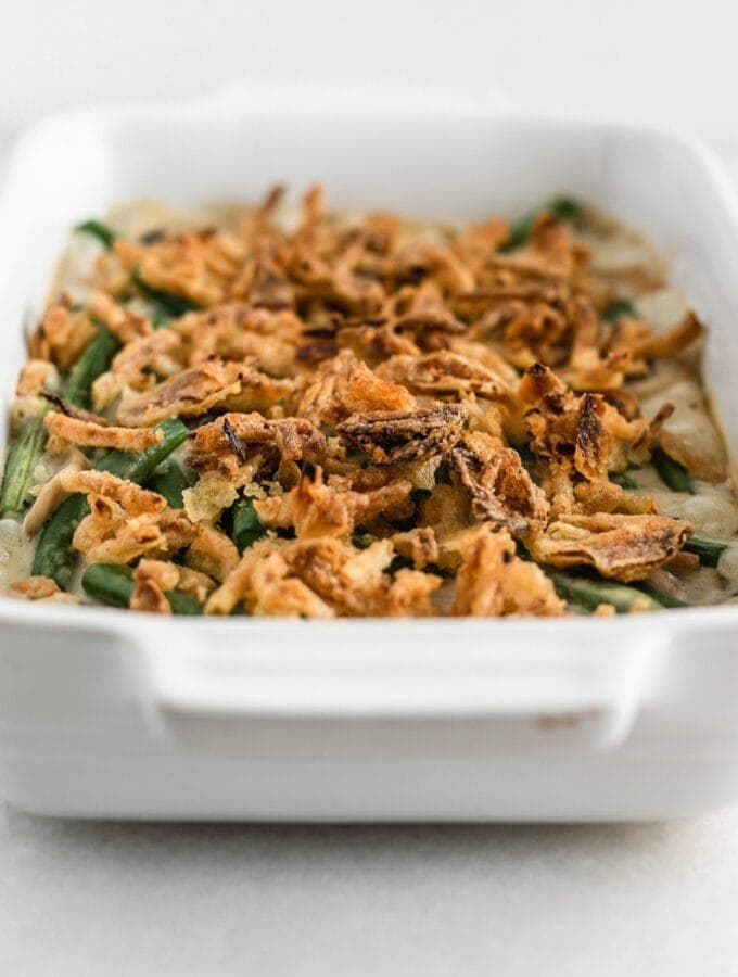green bean casserole topped with crispy onions in a white baking dish.