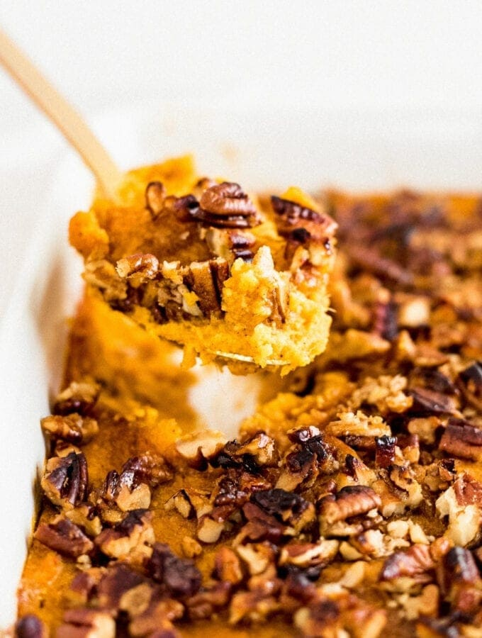 gold spoon lifting pecan sweet potato casserole out of a white dish.
