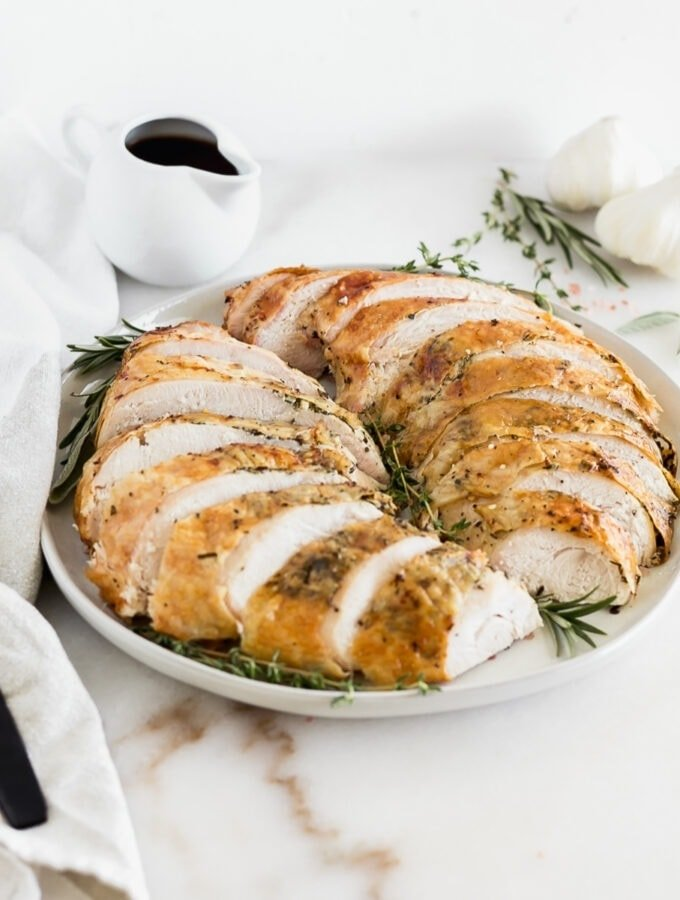 sliced herb roasted turkey breast on a grey platter garnished with fresh herbs.